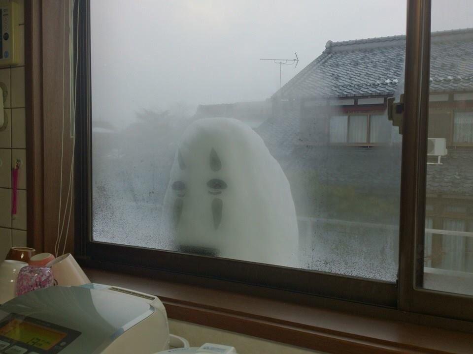 窓から家の中を覗くカオナシ